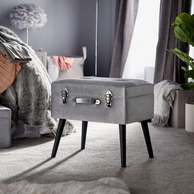 silver storage trunk stool in a grey bedroom